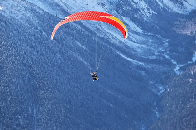 Paravião voando sobre as montanhas nevadas do cáucaso, céu azul ensolarado