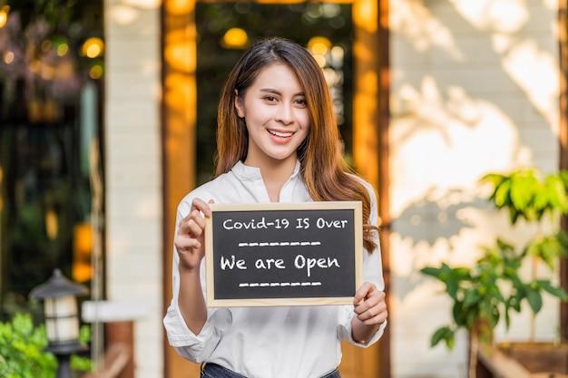 Parceiro asiático proprietário de pequena empresa com as mãos segurando e mostrando o quadro-negro