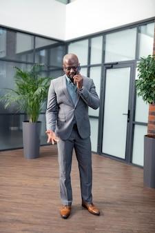Parceiro de chamada. homem de pele escura usando sapatos de couro marrom ligando para seu parceiro de negócios
