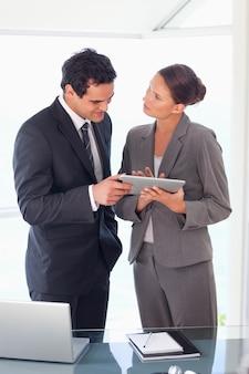 Parceiro de negócios que trabalha no tablet em conjunto