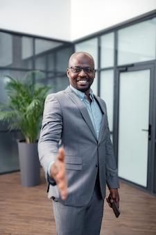 Parceiro de saudação. próspero empresário de pele escura sorrindo enquanto cumprimenta seu parceiro de negócios
