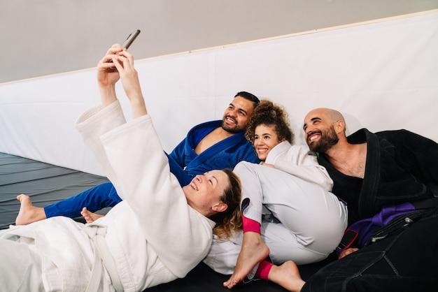 Parceiros de artes marciais como judô usando quimono sentados no carpete do chão e encostados na parede da academia, fazendo uma selfie com o celular muito feliz