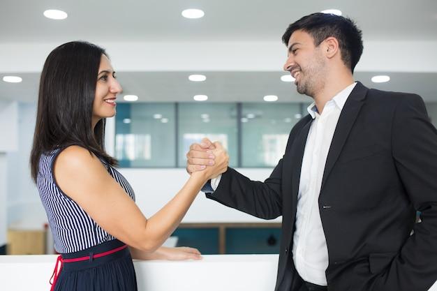Parceiros de negócio bem sucedido feliz fazendo forte aperto de mão