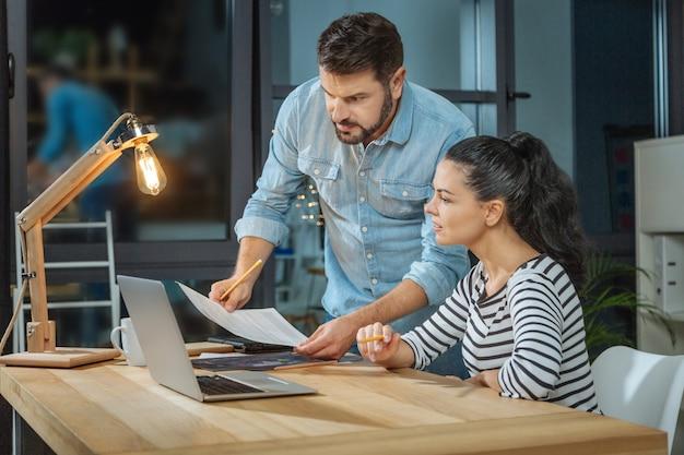 Parceiros de negócios. agradável mulher inteligente e agradável sentada à mesa e olhando para o documento enquanto trabalha com seu parceiro