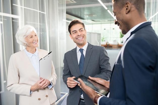 Parceiros de negócios alegres rindo enquanto fala no escritório