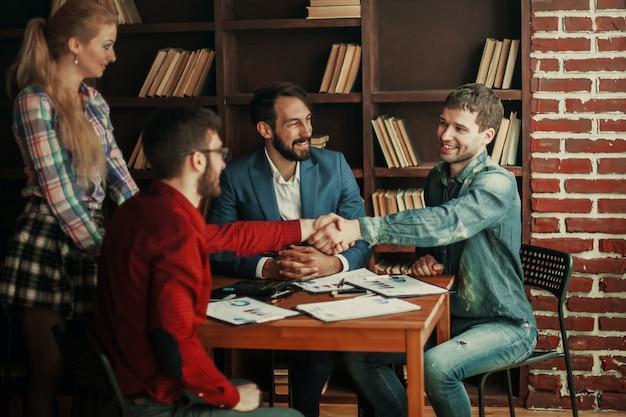 Parceiros de negócios apertam as mãos após discutir o contrato para o espaço de trabalho no escritório