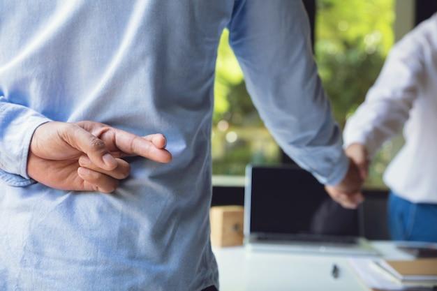 Parceiros de negócios, apertando as mãos com um deles segurando os dedos cruzados nas costas.