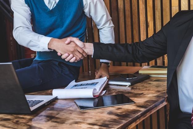 Parceiros de negócios bem sucedido, apertando as mãos, terminando uma reunião.