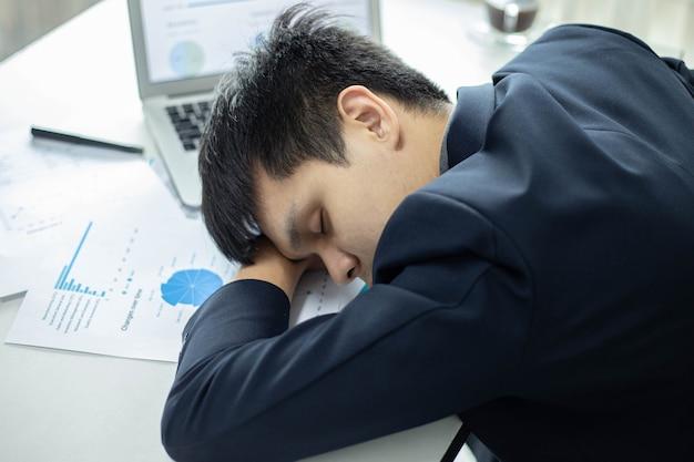 Parceiros de negócios conceber um homem de negócios jovem masculino dormindo em uma mesa com um laptop e um documento depois de trabalhar por muito tempo.