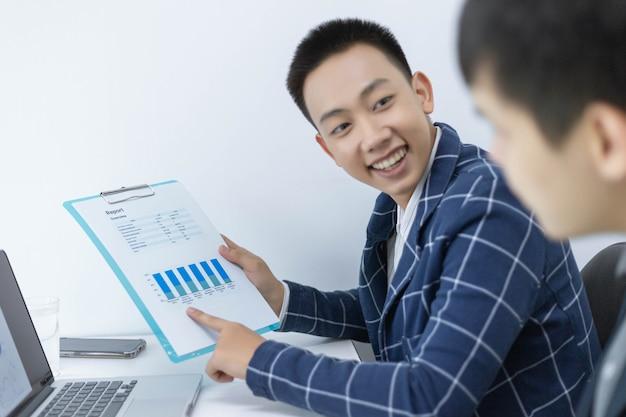 Parceiros de negócios conceber um jovem empresário apontando para o resumo do lucro do último mês, mostrando em formulários de documentos.