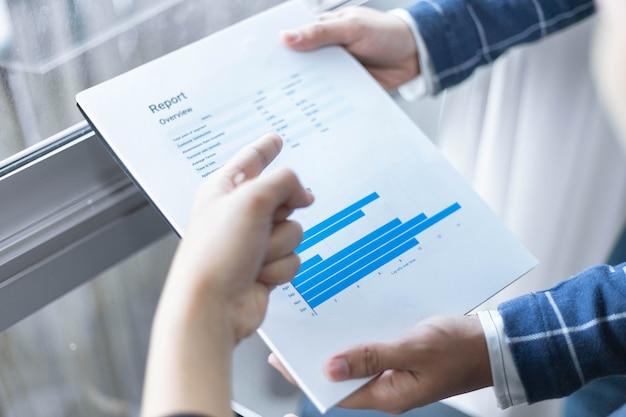 Parceiros de negócios conceituam um jovem empresário, criando um resumo do lucro dos últimos meses, mostrando em formulários de documentos.