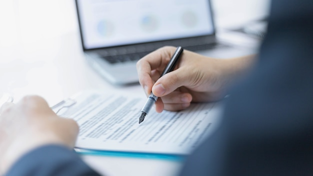 Parceiros de negócios conceituam um jovem empresário que assina um contrato com uma grande empresa.