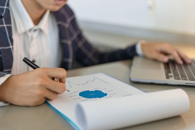 Parceiros de negócios conceituam um jovem empresário usando um laptop, revisando o resumo de vendas anual.