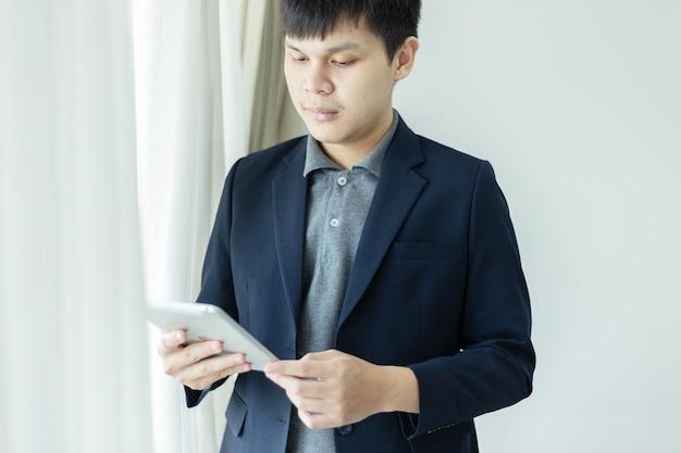 Parceiros de negócios conceituam um jovem empresário vestindo paletó marinho, olhando para a tela do tablet, verificando uma caixa de entrada de e-mail.