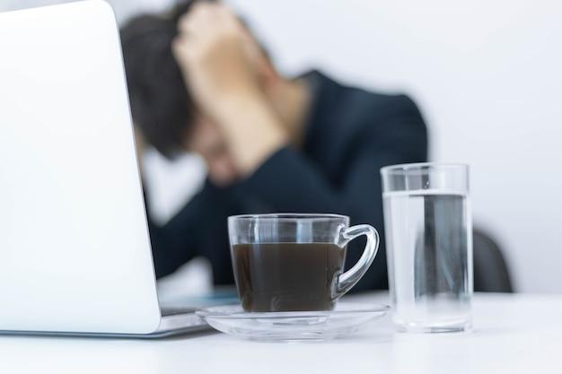Parceiros de negócios conceituam uma xícara de café sobre uma mesa branca com um plano de fundo de um empresário estressado com o trabalho.