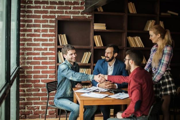 Parceiros de negócios confiáveis apertam as mãos após discutir o contrato para o espaço de trabalho no escritório