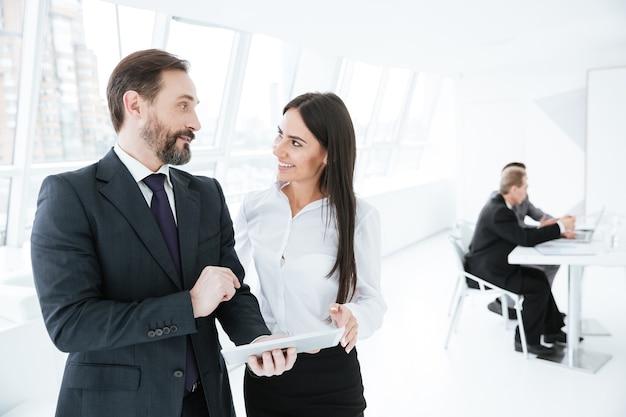 Parceiros de negócios conversando no escritório com colegas