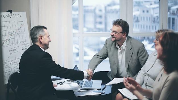 Parceiros de negócios de aperto de mão após discussão do contrato