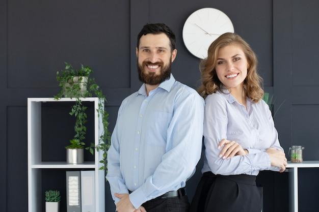 Parceiros de negócios de sucesso com um jovem e uma mulher posando de costas um para o outro.