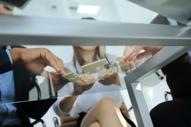 Parceiros de negócios de visão inferior responsáveis pelas peças do quebra-cabeça