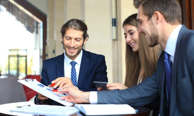 Parceiros de negócios discutindo documentos e ideias na reunião.