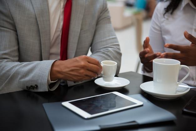 Parceiros de negócios, discutindo questões de trabalho com uma xícara de café