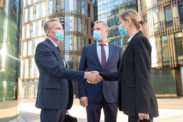Parceiros de negócios em máscaras, apertando as mãos perto de prédios de escritórios, encontrando-se e conversando na cidade. vista lateral, ângulo baixo. conceito de comunicação e coronavírus