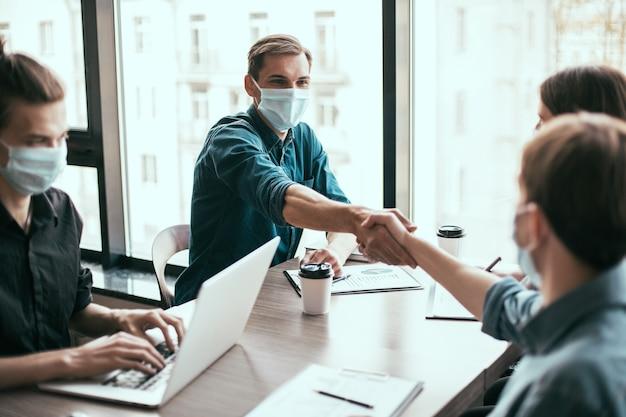 Parceiros de negócios em máscaras protetoras, apertando as mãos uns dos outros.