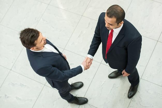 Parceiros de negócios estão apertando as mãos como um símbolo de unidade.
