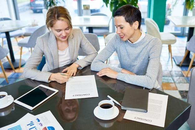 Parceiros de negócios femininos, assinando contrato