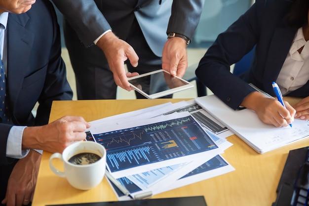 Parceiros de negócios irreconhecíveis que trabalham com gráficos estatísticos. empresário segurando o tablet. empresária de conteúdo profissional fazendo anotações para estatísticas. conceito de comunicação e parceria