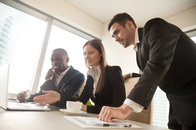 Parceiros de negócios multirraciais usando laptop durante reunião, looki