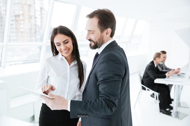 Parceiros de negócios olhando para um tablet no escritório com colegas