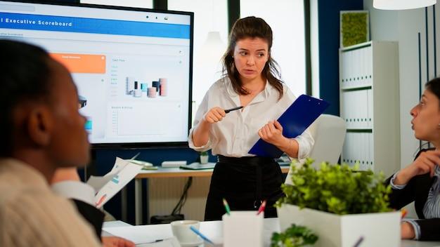 Parceiros de negócios planejando estratégia em conferência de reunião, trabalhando com lousa digital interativa, discutindo estatísticas de projeto, compartilhando ideias. equipe corporativa falando sobre novo aplicativo de negócios