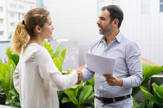 Parceiros de negócios positivos terminando reunião com aperto de mão