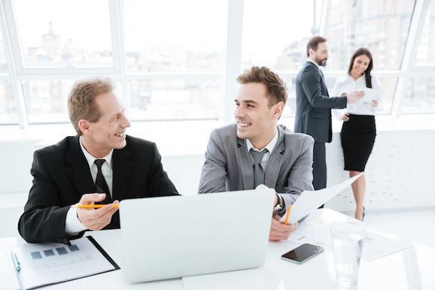 Parceiros de negócios rindo sentados à mesa com laptop e documentos com colegas