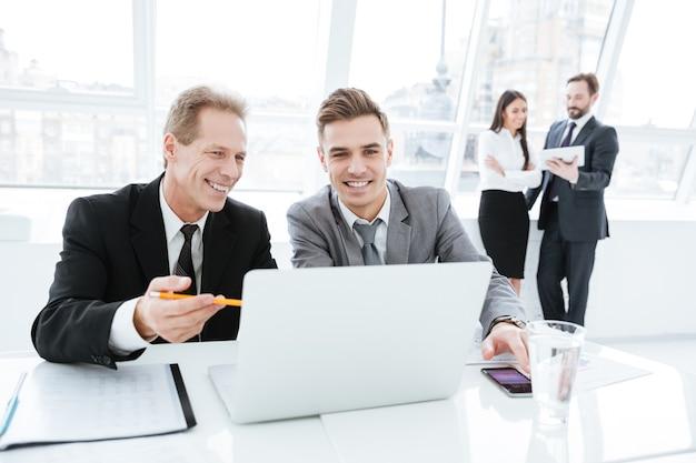 Parceiros de negócios sentados à mesa com laptop no escritório com colegas