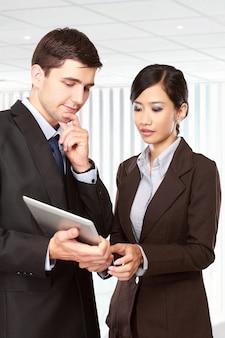 Parceiros de negócios usando o touchpad na reunião