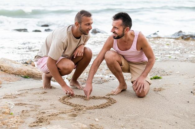 Parceiros de tiro completo desenhando um coração na areia