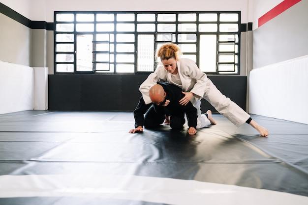 Parceiros em um treinamento de artes marciais com quimonos praticando técnicas no tapete de ginástica, todos usando máscaras faciais devido ao desejo.