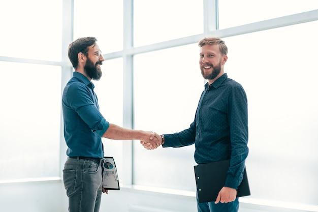 Parceiros financeiros apertando as mãos em pé no escritório