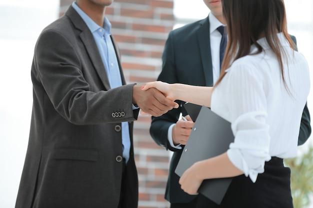 Parceiros financeiros do aperto de mão do close up .business no fundo do escritório. o conceito de parceria