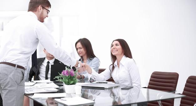Parceiros homem e mulher apertando as mãos sobre a mesa, mantendo o contato visual.