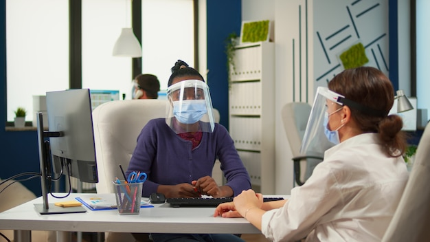 Parceiros multiétnicos trabalhando no escritório com um novo normal sentado na mesa em frente ao computador discutindo estratégia usando máscaras de proteção. grupo de diversos empresários que respeitam a distância social.