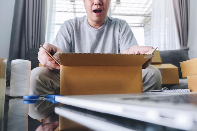 Parcela da empresa de pequeno porte para o transporte, homem feliz que abre a caixa em linha do pacote da compra com o pacote ao sentar-se no sofá em casa