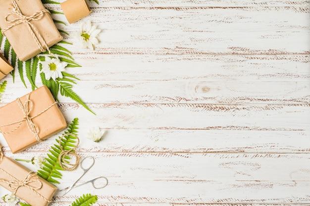 Parcela marrom amarrada com corda e flor branca na mesa