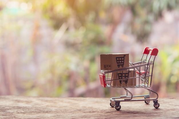 Parcele ou caixas de papel com um logotipo de carrinho de compras em um carrinho na mesa de madeira.