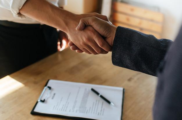 Parceria. aperto de mão de duas pessoas de negócios após a assinatura do contrato no escritório da sala de reuniões