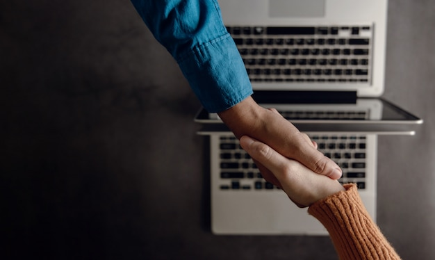 Parceria de negócios ou trabalho em equipe fazendo aperto de mão. negócio bem-sucedido após reunião. vista do topo. mesa de trabalho turva com laptop