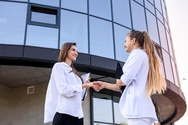 Parceria. duas jovens empresárias apertando a mão do lado de fora do prédio de escritórios